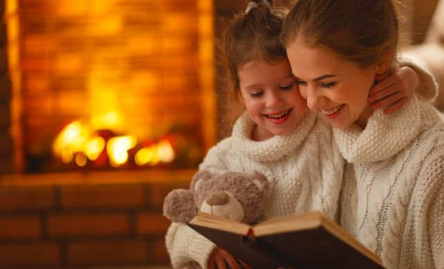 Mother Reading Book to Her Daughter with a Warm and Working Furnace