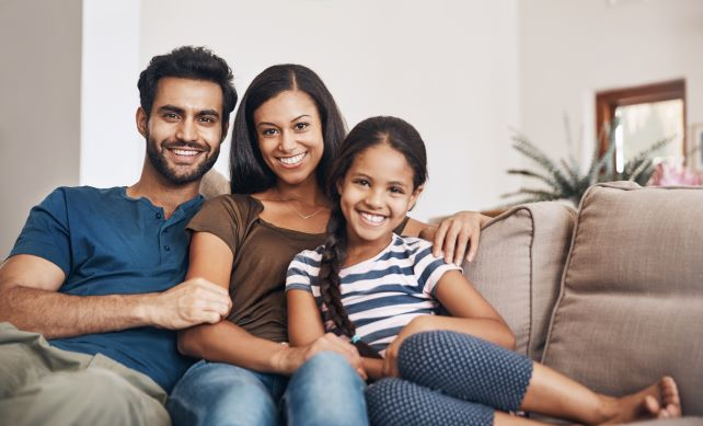 Family sitting on couch together smiling
