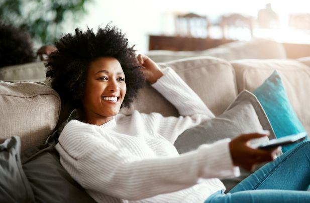 Woman relaxing on couch watching tv