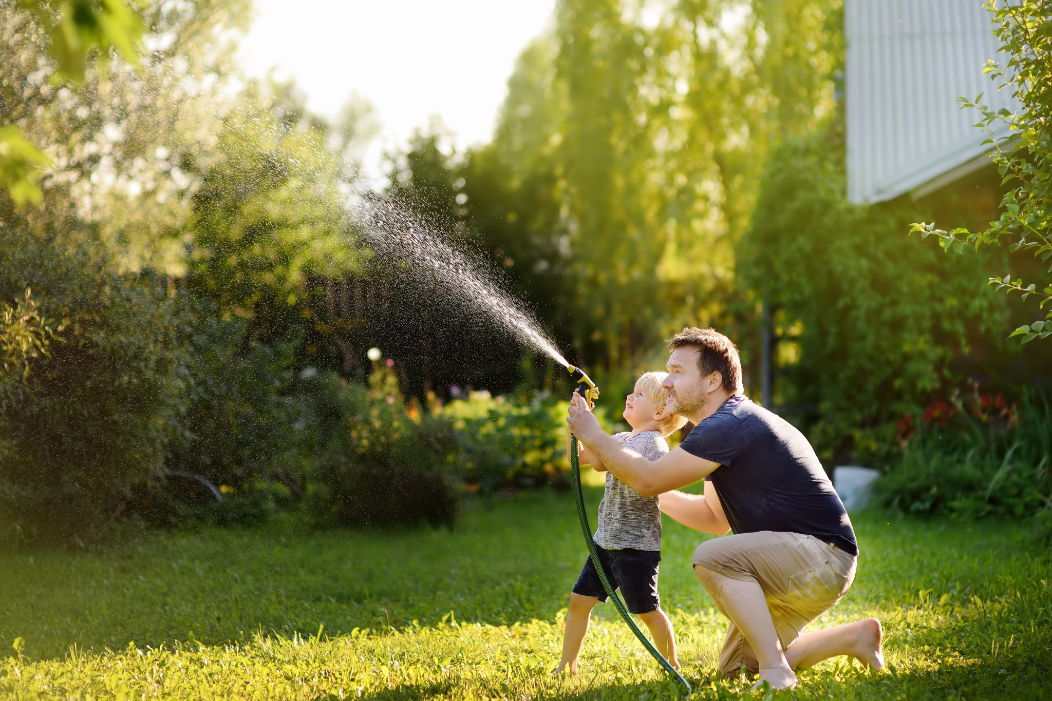 Funny little boy with his father playing with garden hose in sunny backyard