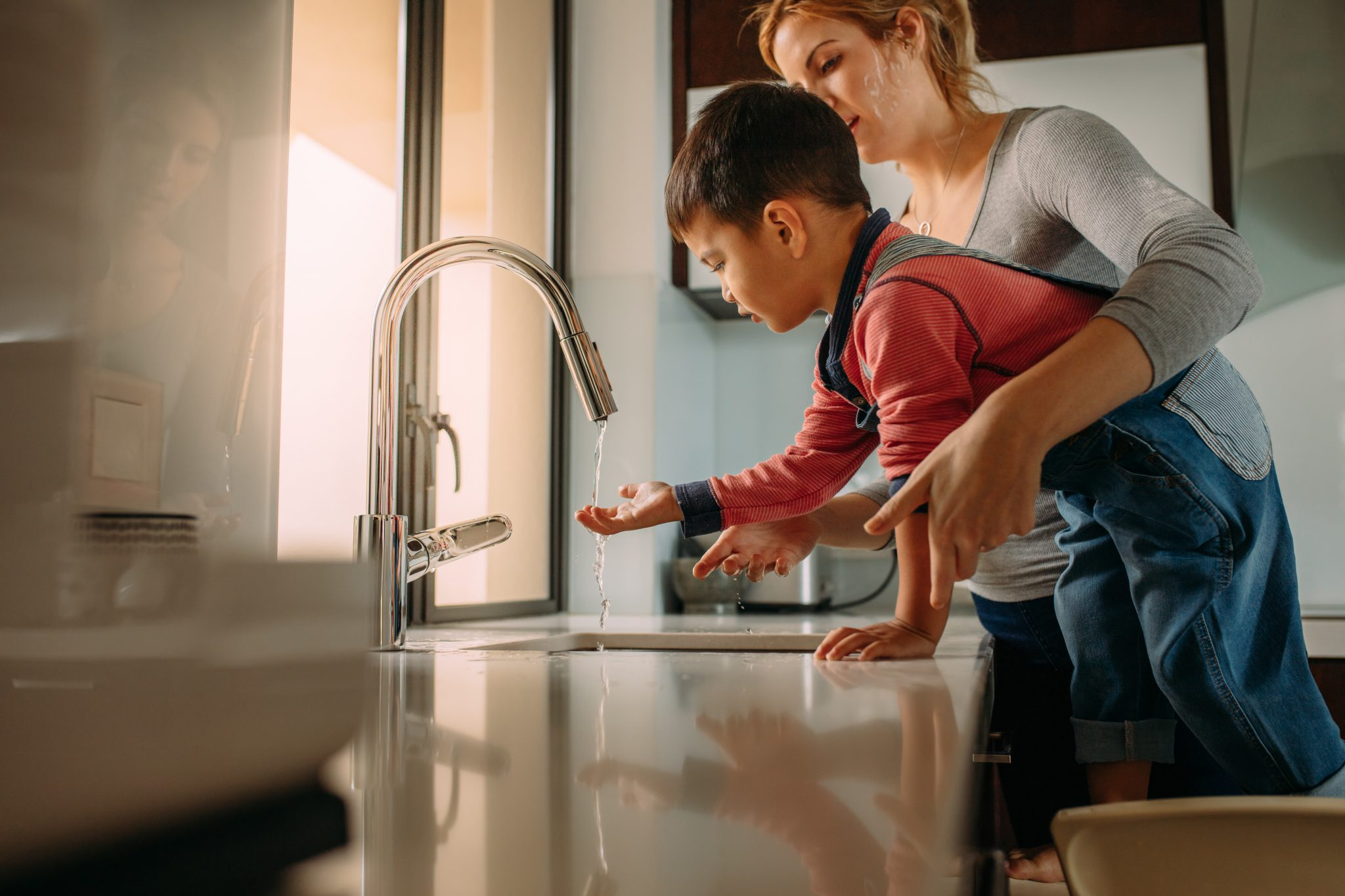 Mom helping son wash hands