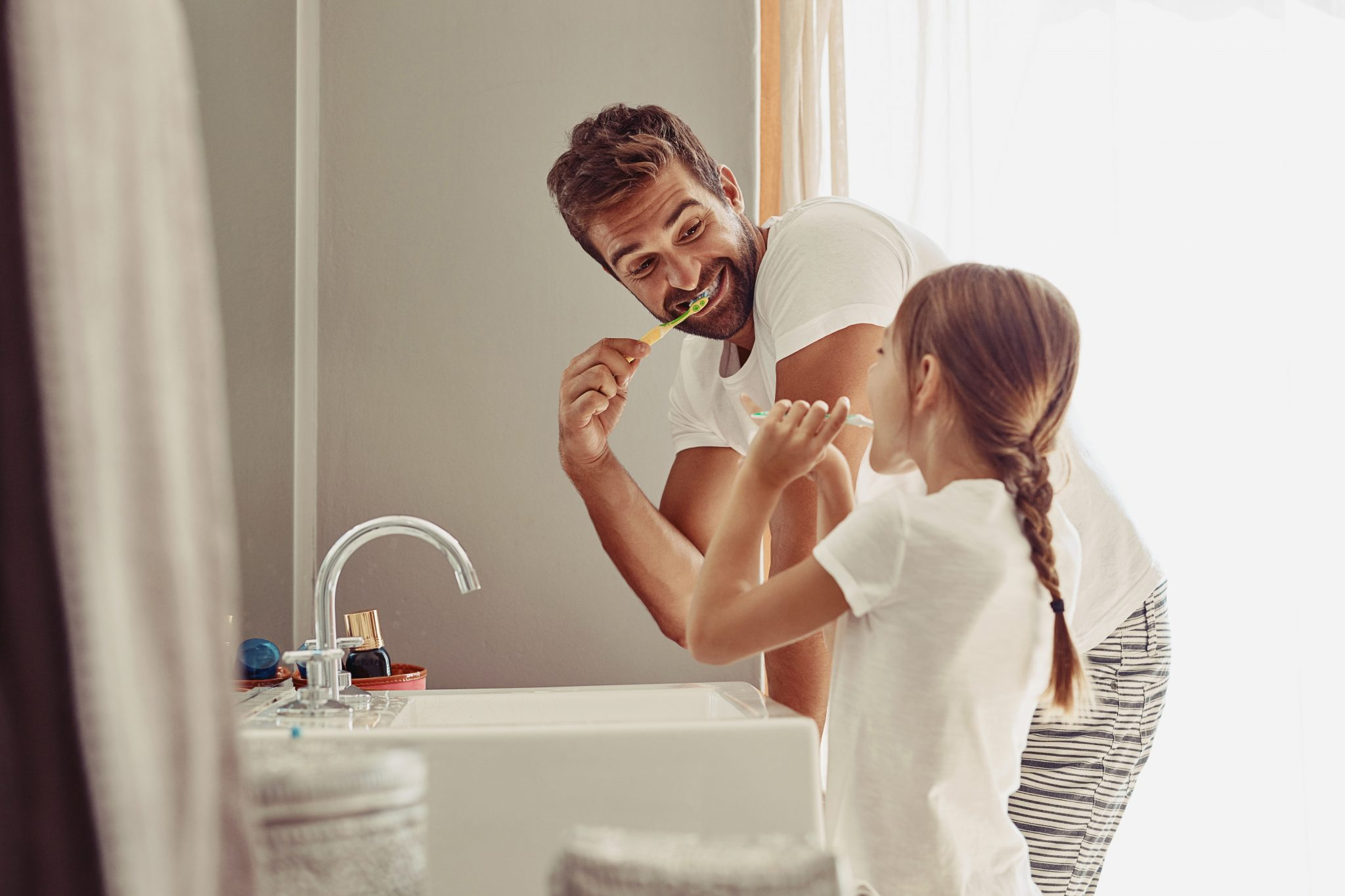 Dad and daughter brushing teeth