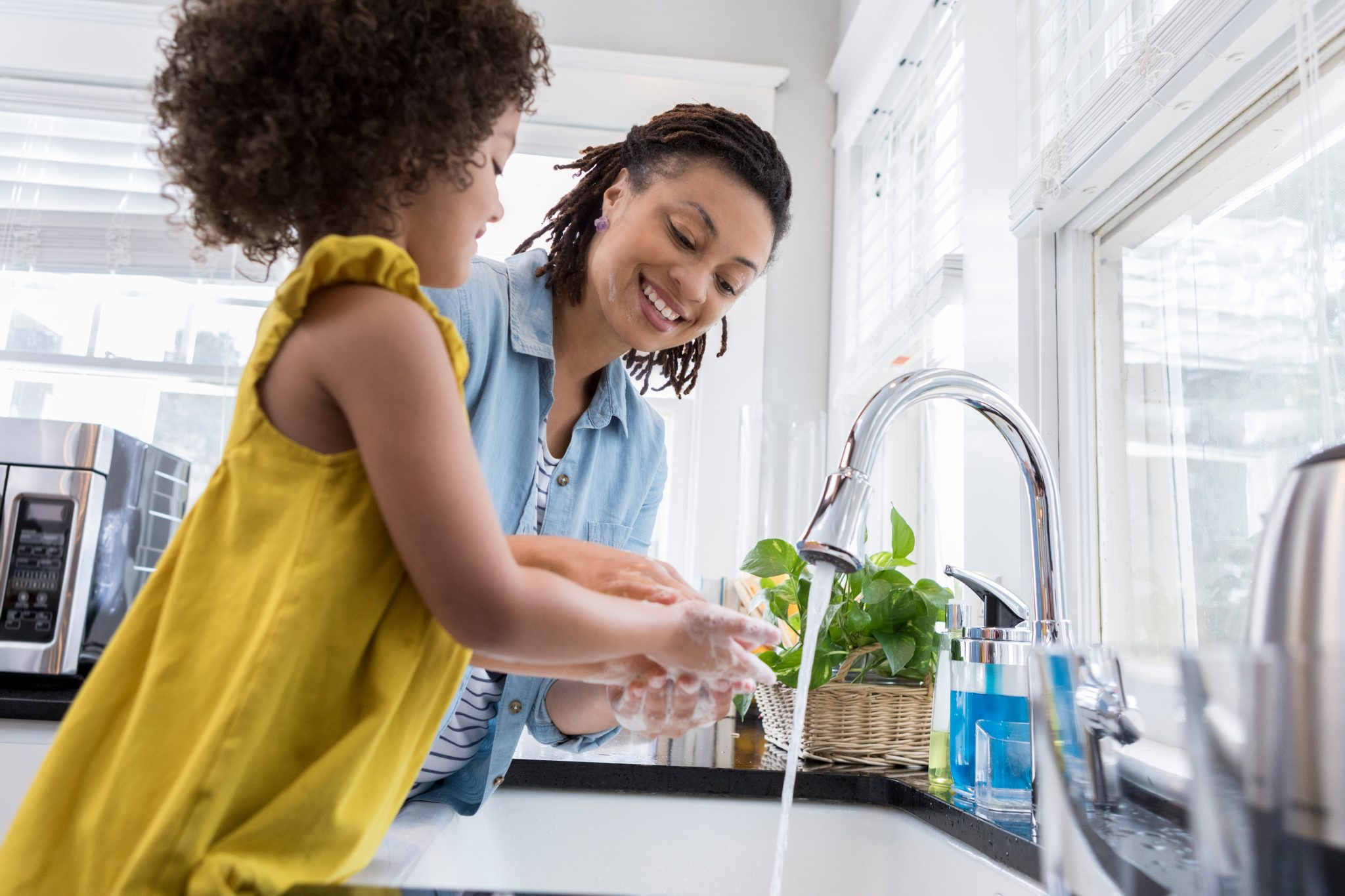 Mom helping daughter wash hands