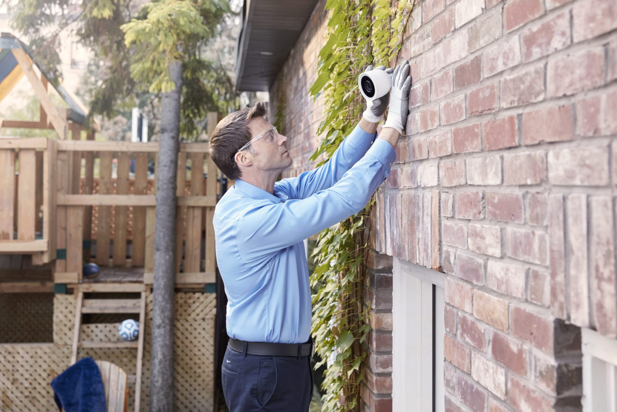 Reliance Technician installing Google Nest Cam on outside of house