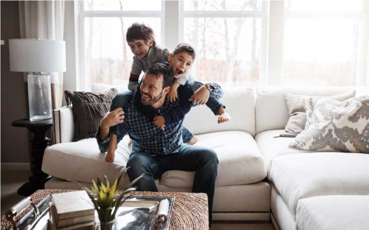 Dad playing with sons on couch