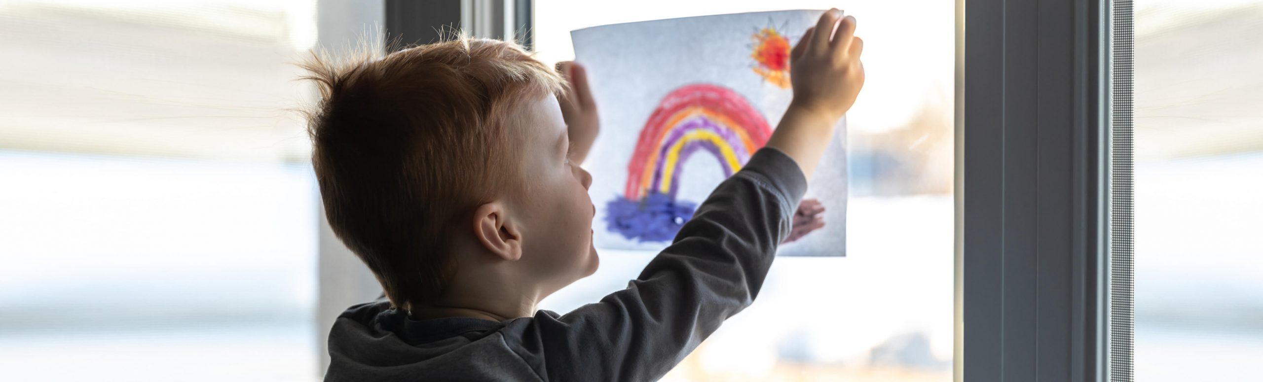 Young boy holding up his drawing to the window.
