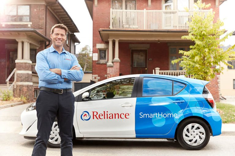 Smart Home Technician standing in from of Reliance car