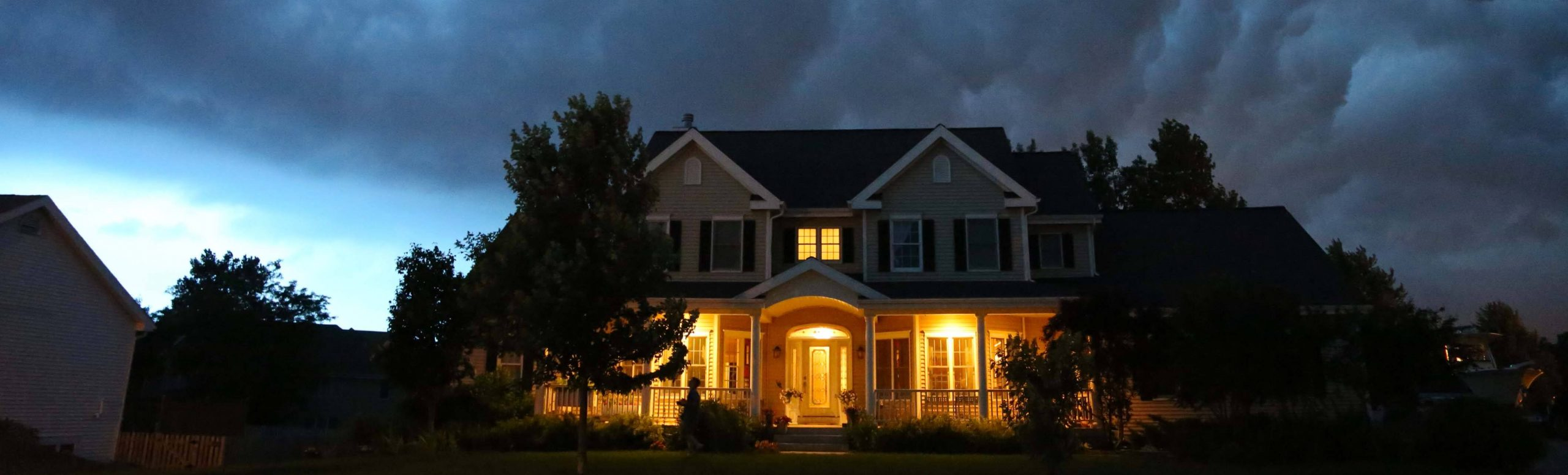 Exterior of a house with dark storm clouds overhead