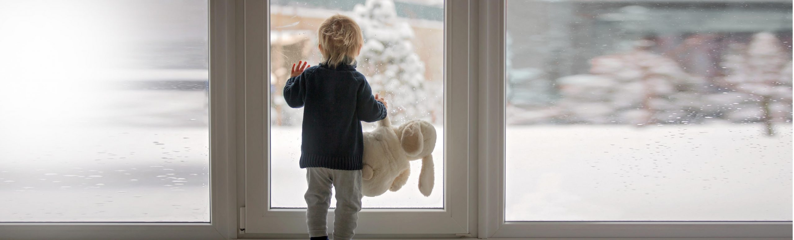 toddler holding teddy bear looks out window at snow